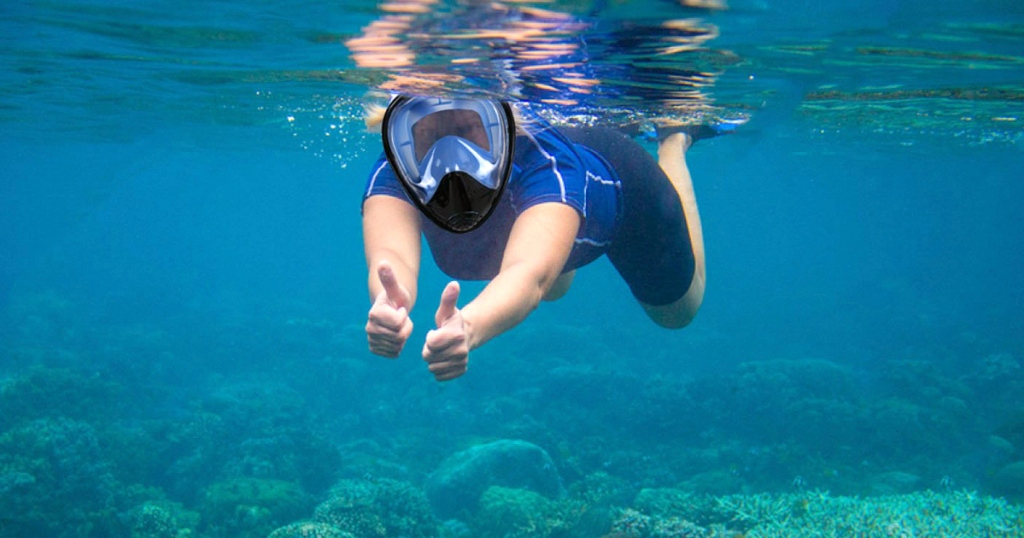 person snorkeling underwatergiving thumbs up