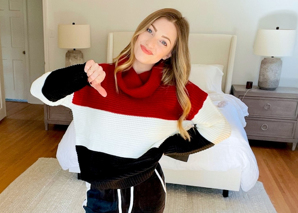 woman holding a thumbs down wearing color block sweater