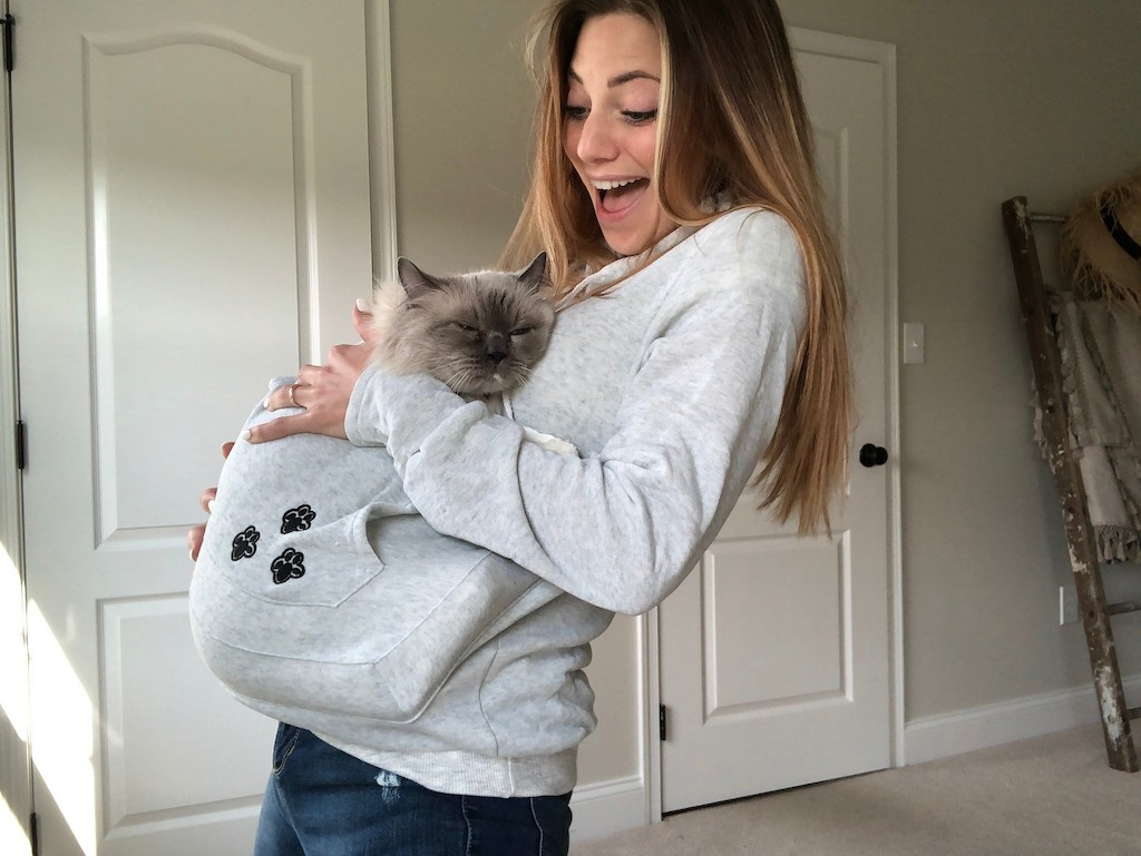woman wearing hoodie with cat inside pouch