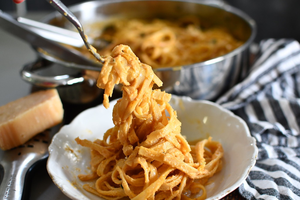 pumpkin alfredo in bowl with noodles being twirled on fork