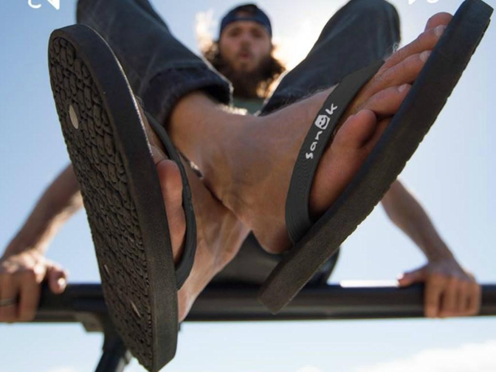 man wearing black sanuk flip flops crossing legs