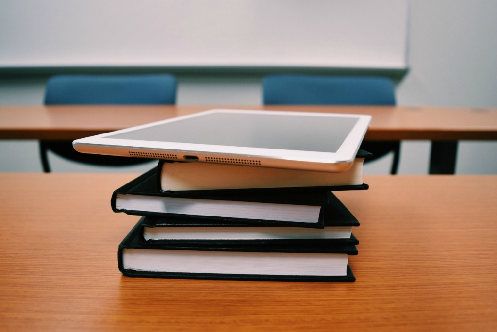 stack of textbooks and ipad in classroom