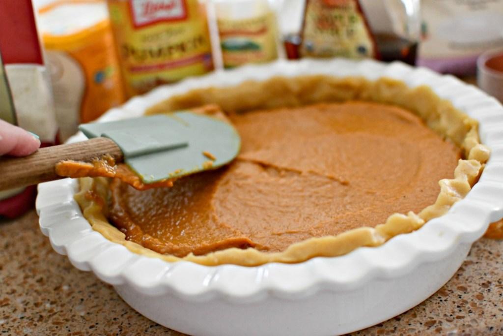 spreading a pumpkin pie before baking