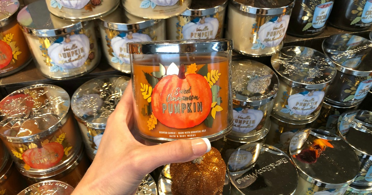 hand holding pumpkin candle