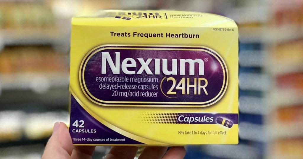 hand holding nexium capsules at target