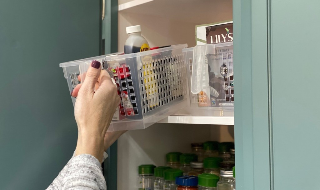 hand holding pulling out clear basket from cabinet