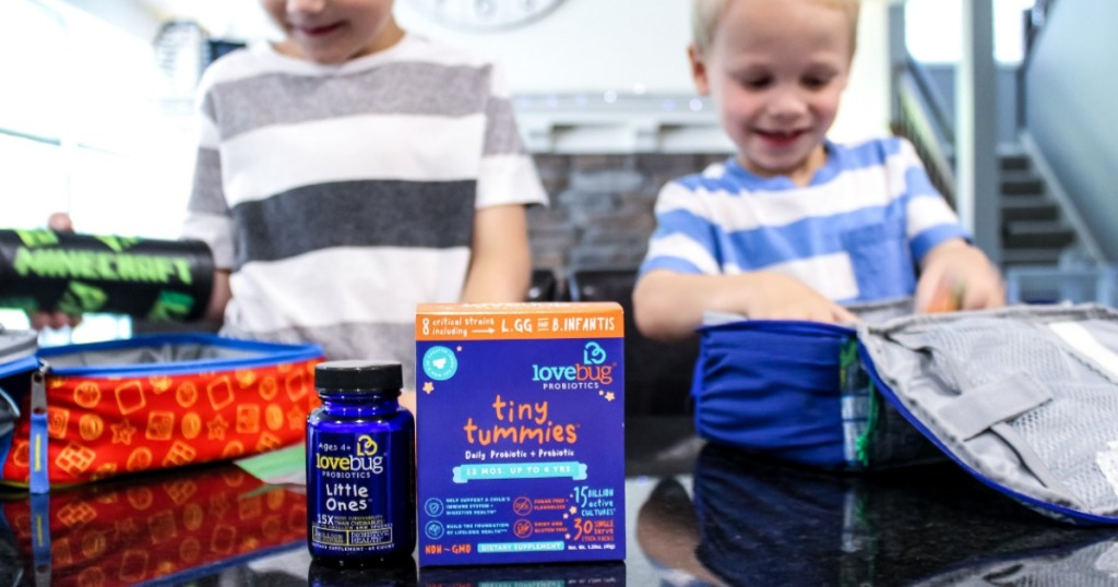 kids packing school lunches with tiny tummies box in front of them