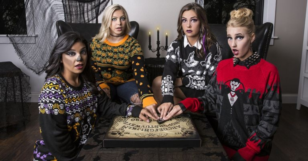 4 women wearing ugly Halloween sweaters