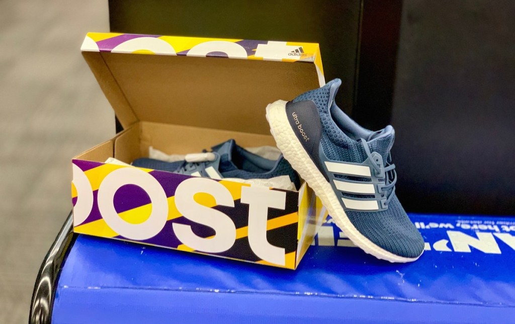 blue adidas sneakers and yellow box sitting on blue bench