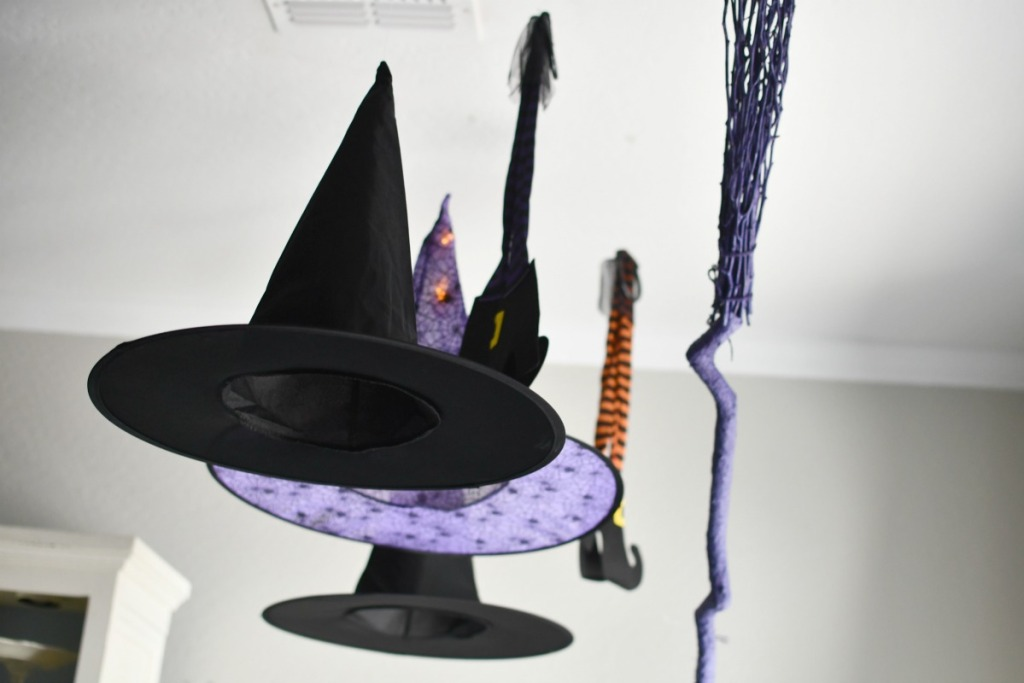 witch hat hanging with lights and a broom