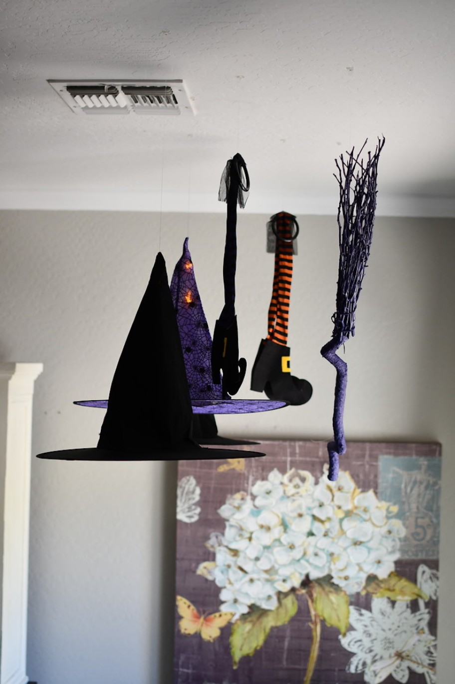 witch hats and broom hanging from ceiling