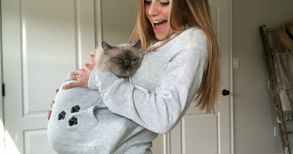 woman wearing light gray sweatshirt hoodie with cat inside