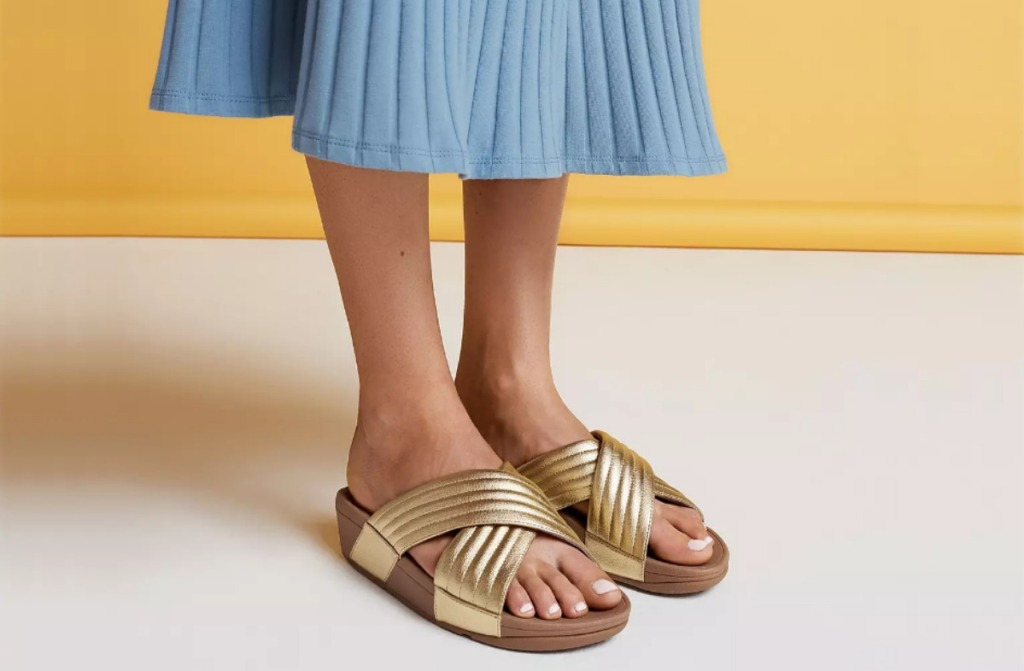 oman in blue chambray skirt wearing gold slides