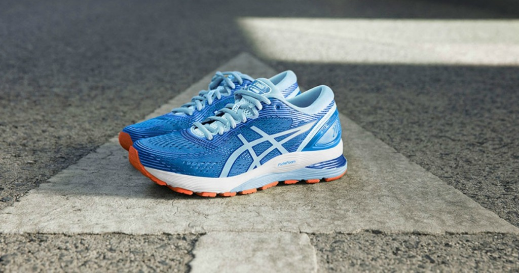 blue and white asics shoes on road arrow