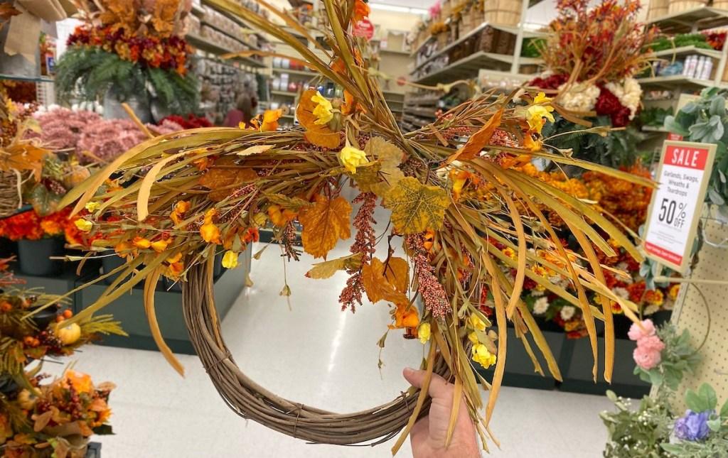 hand holding a fall wreath in hobby lobby