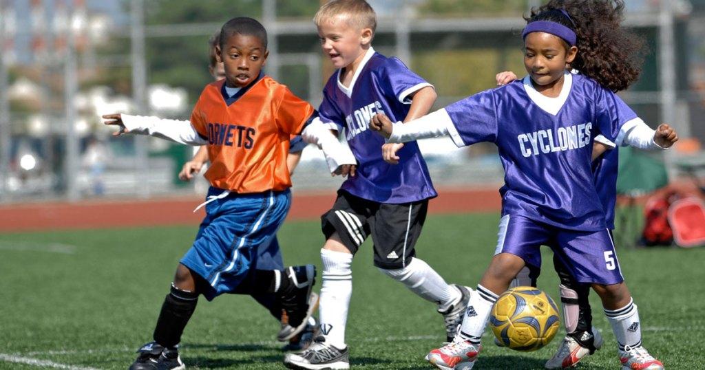 kids playing soccer wearing jerseys