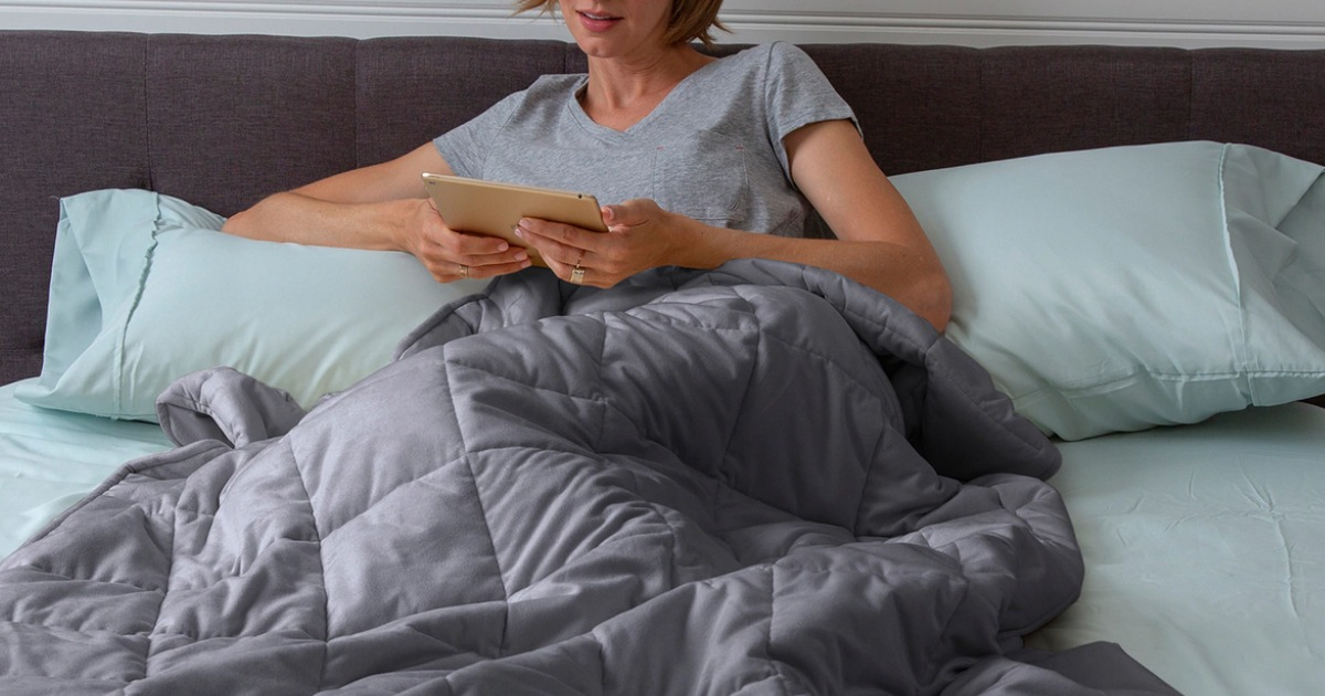 Woman in bed covered in 15 lb Tranquility Weighted Blanket