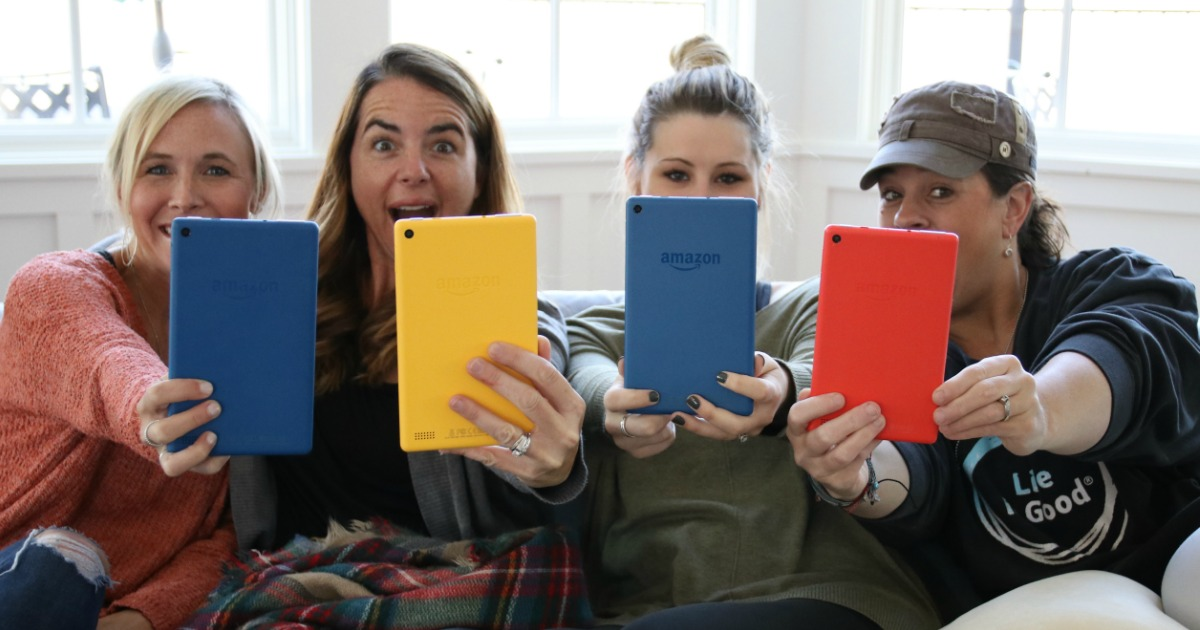 four women sitting together and holding up kindles
