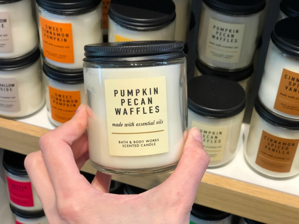 Holding a single wick fall scent candle in store at Bath & Body Works