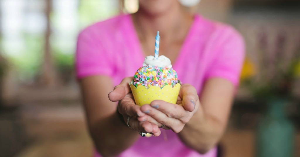 Woman holding cupcake with candle