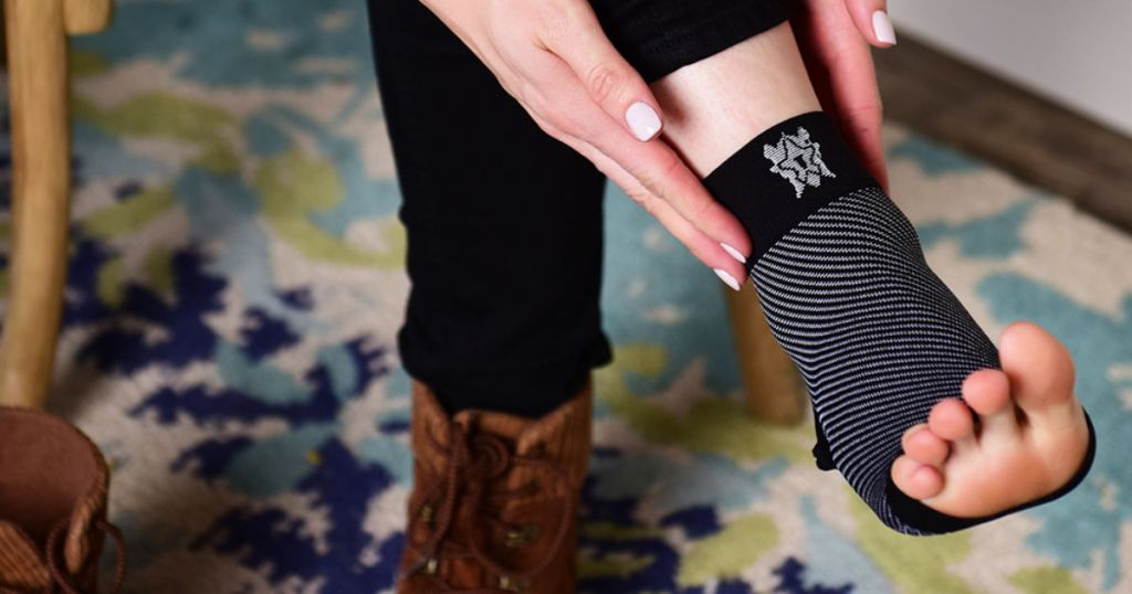 woman putting on black Bitly Plantar Fasciitis Sock