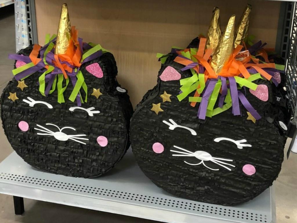black cat unicorn pinatas on store shelf