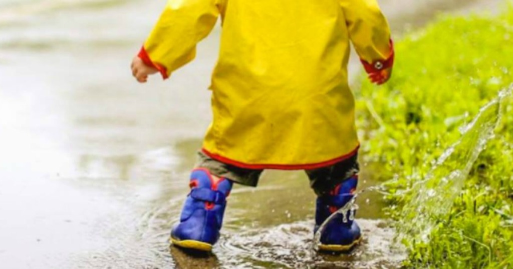boy splashing in puddles with Bogs Boots