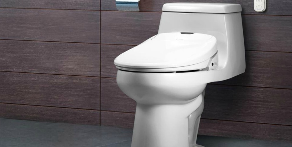 Electric bidet attached to a toilet in a bathroom