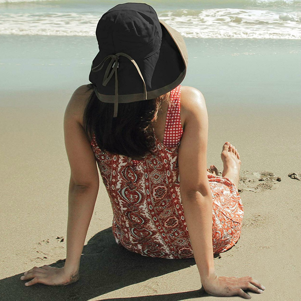 Woman wearing a black and beige sun hat in the sand at the beach