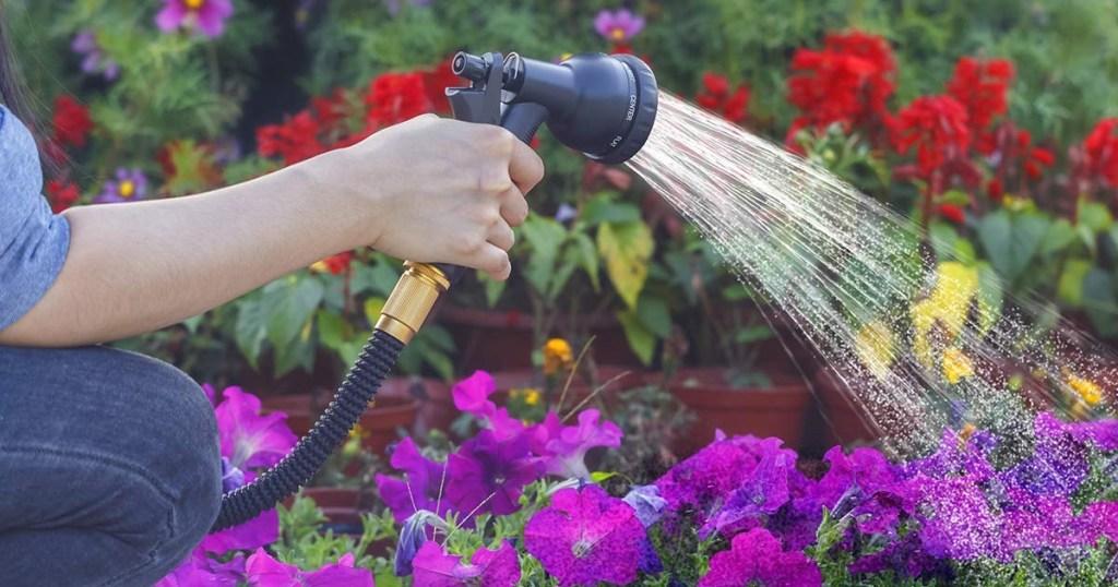 woman spraying garden hose on flowers