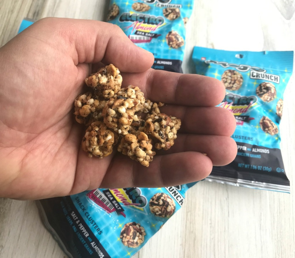 Man's hand holding CLIF bar brand almond snacks
