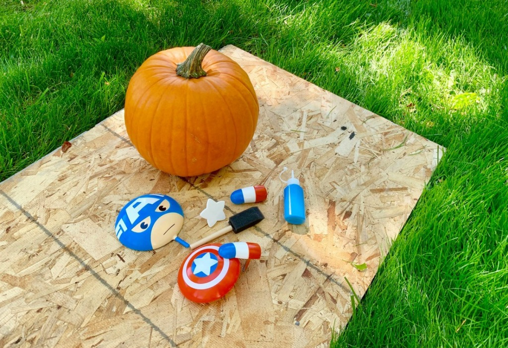 Captain America no-carve pumpkin pieces and pumpkin outside on plywood