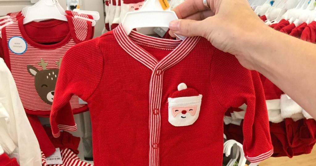 Woman holding Carter's Holiday Themed Pajamas in store