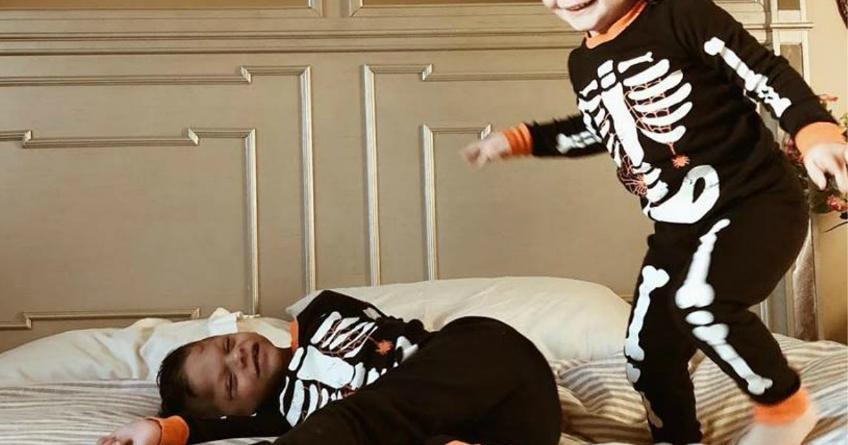 kids jumping on bed wearing halloween pjs