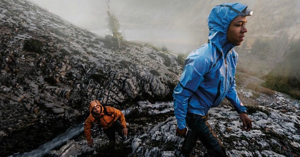 Men wearing rain jackets on a rough terrain hike.