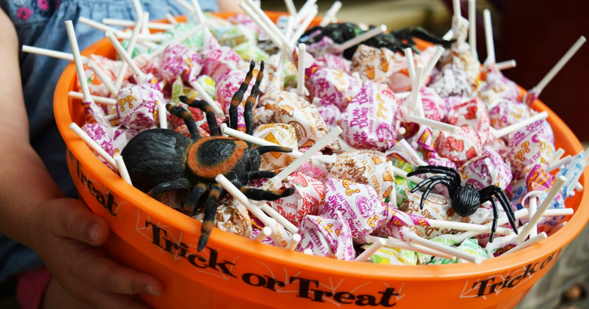 Dum Dums lollipops in trick or treat bowl with plastic spiders