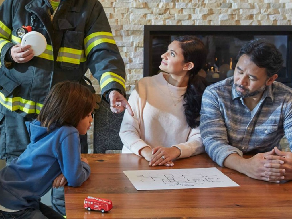 firefighter and family talking about alarm systems