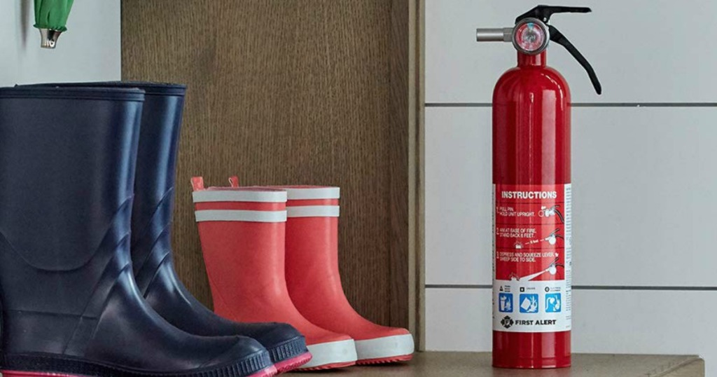 Fire extinguisher on counter near boots in home