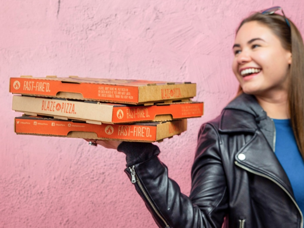Girl holding blaze pizza boxes