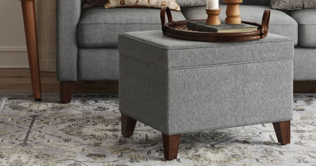 gray ottoman with tray sitting on top on it with area rug underneath in and couch in background
