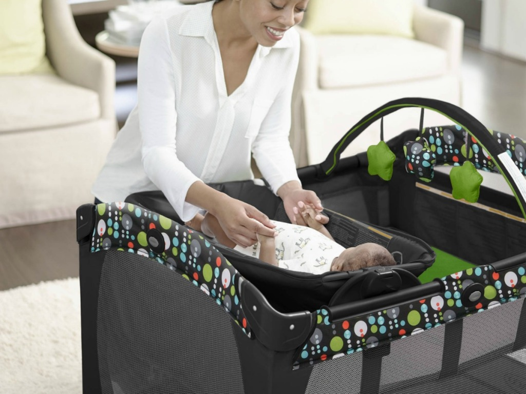 mom laying baby in Graco playard