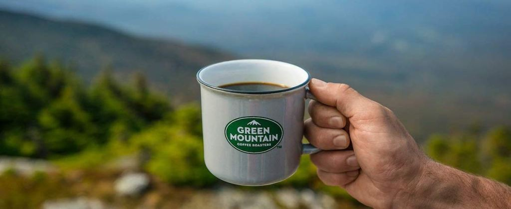 person holding green mountain coffee mug