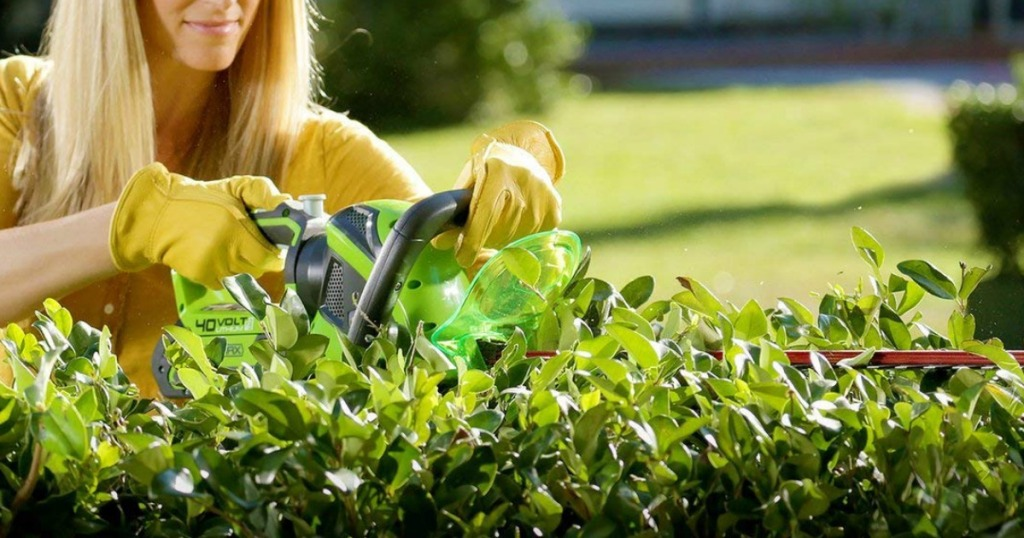 woman trimming bushes with Greenworks Trimmer