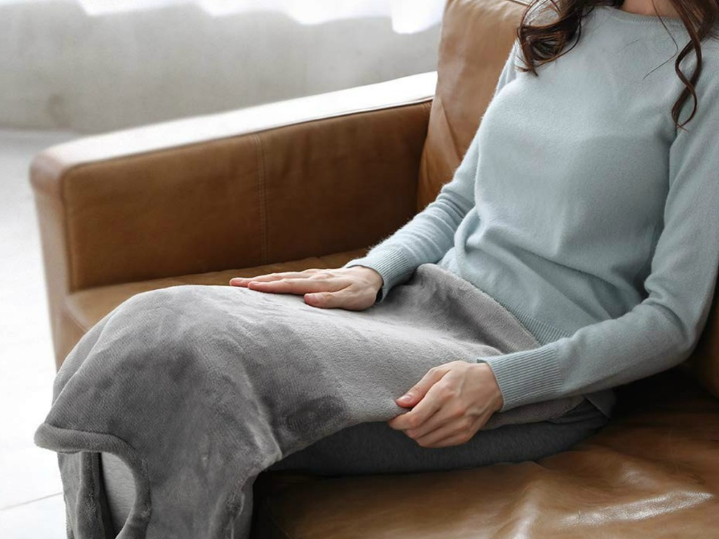 lady sitting on a couch with a heated blanket on her lap