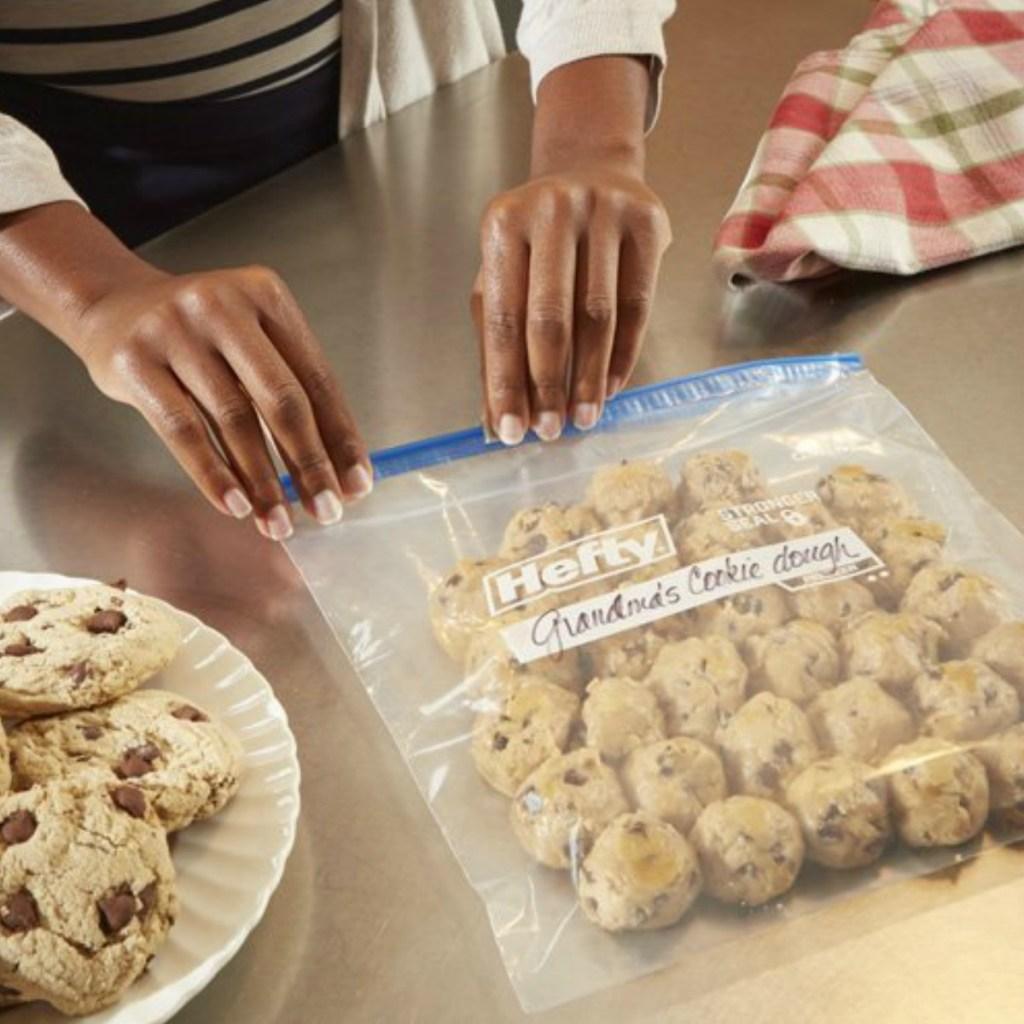 Woman closing Hefty Gallon freezer bag with cookie dough balls inside