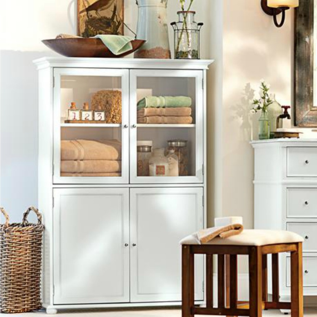 White bathroom cabinet with linens inside