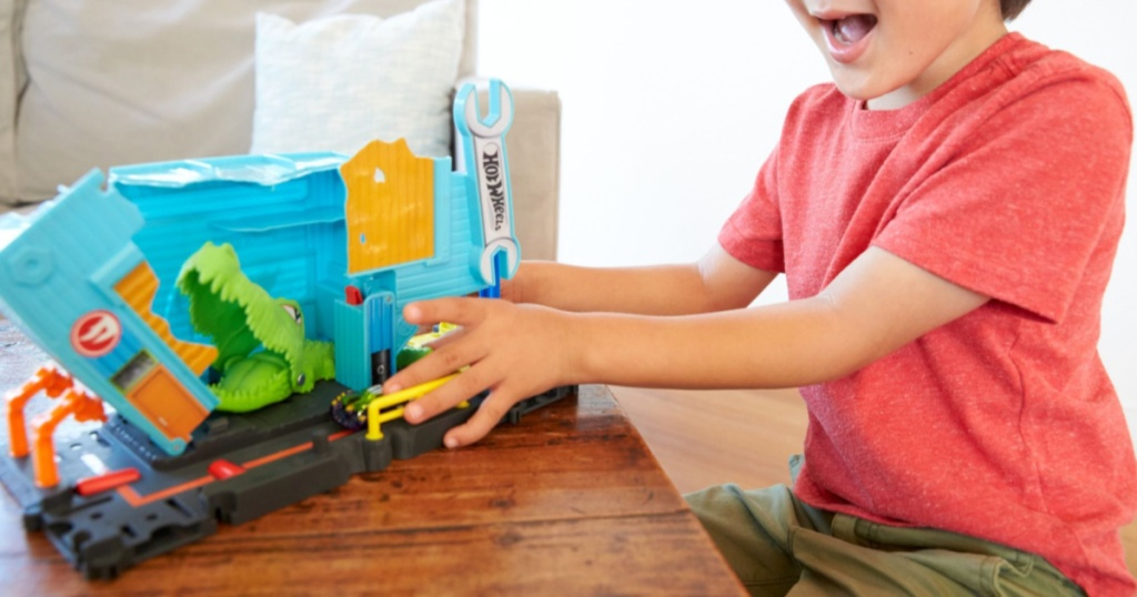 kid playing with hot wheels city nemesis play set