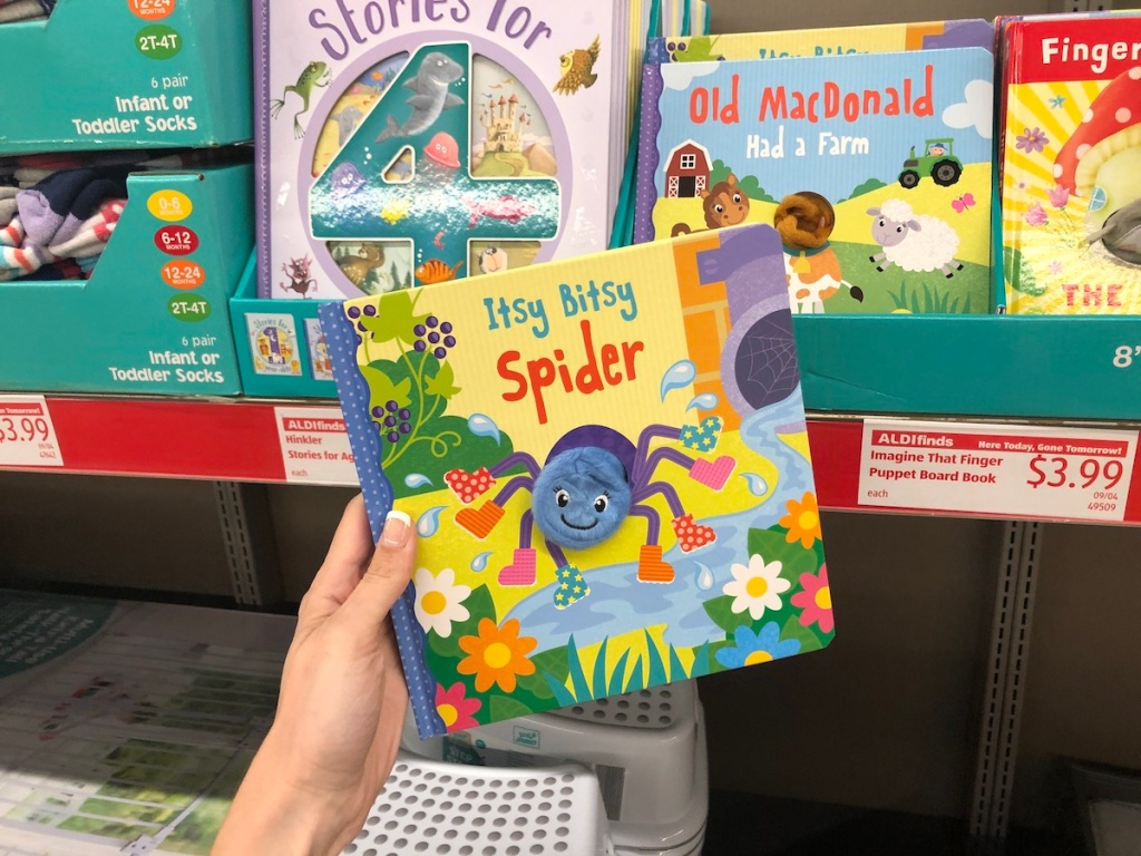 Woman holding Imagine That Finger Puppet Board Book in ALDI