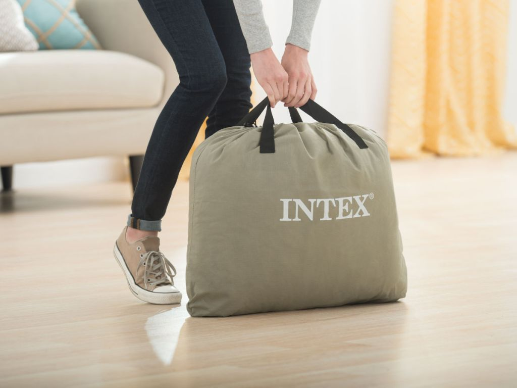 person holding Intex Queen Airbed bag in living room