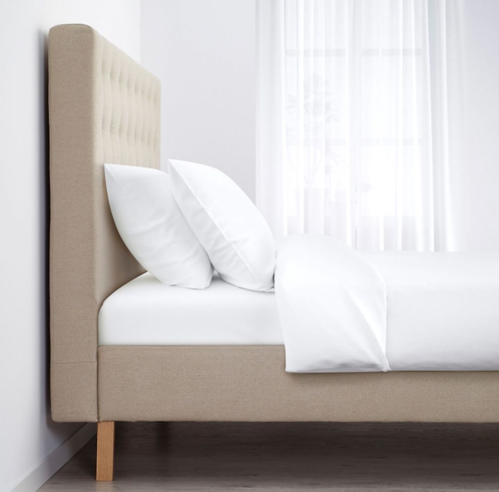 tufted upholstered KVALFJORD IKEA bed frame with white bedding